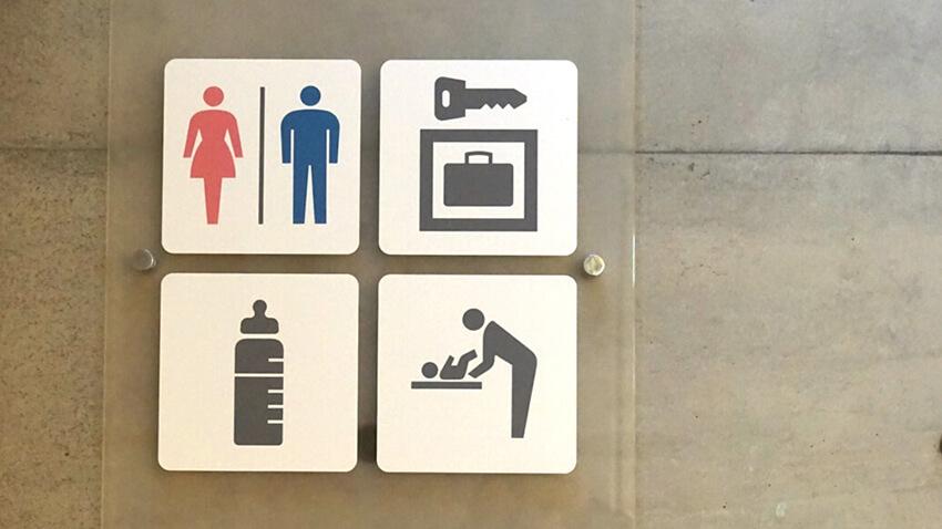 表参道ヒルズで使用されている、男女のトイレ、コインロッカー、授乳室、おむつ交換台のピクトグラムのサインの写真。