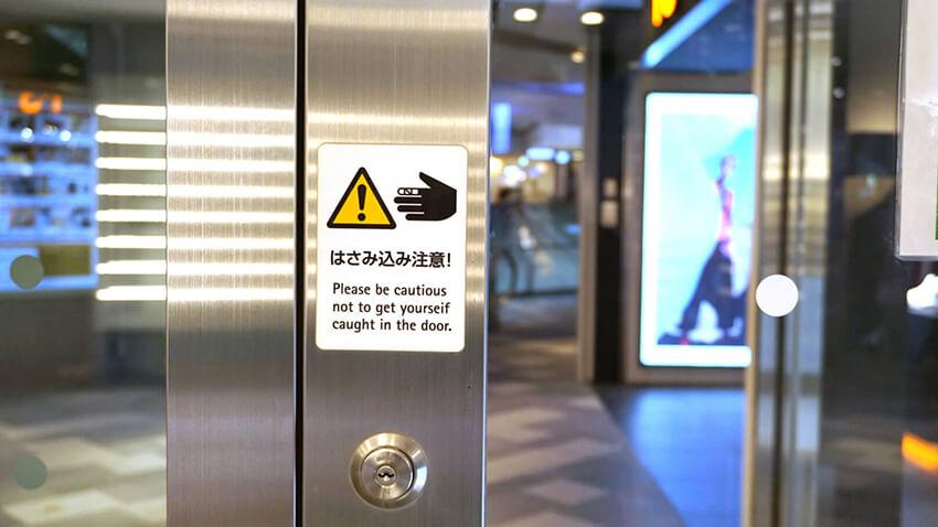 表参道ヒルズで使用されている、自動ドアに指はさみ込み注意のピクトグラムのサインの写真。