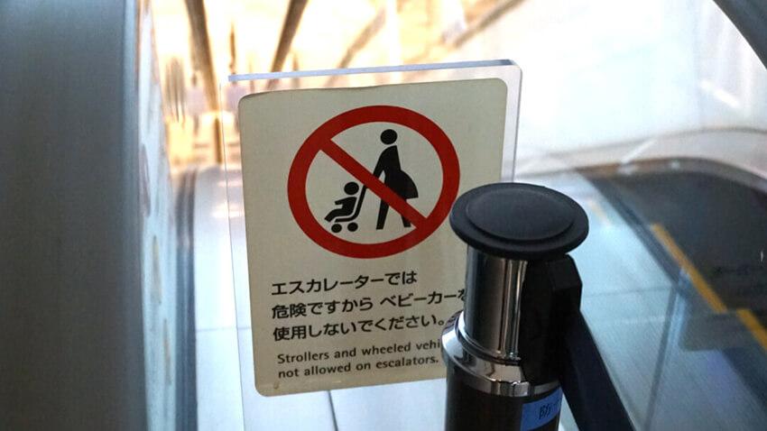 表参道ヒルズで使用されている、エスカレーターでのベビーカー使用禁止のピクトグラムのサインの写真。